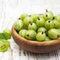 Gooseberry with leaves on a wooden background