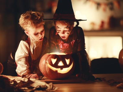 happy children in costumes of witch and vampire in a dark house in halloween